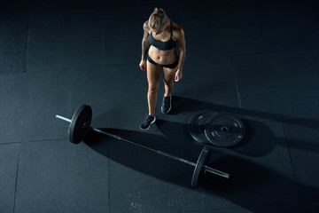 Barbell girl Barbell on gym floor. Weigh lifting. Bench press. View from above, dark background Bright side light, sharp shadow. Heavy weight exercises.