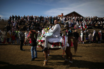 Bulgarian Muslim man carries his son on a horse as they attend a ritual ahead of a mass circumcision ceremony in the village of Ribnovo