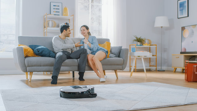 Smart Robot Vacuum Cleaner Sucking Up Dust from a Carpet. Beautiful Couple is Sitting on a Sofa and Talking in the Background. Technological Home Appliance Device Moves Past Them.