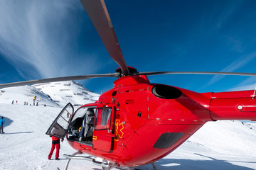 Fotorollo Hubschrauber red rescue helicopter stands on the snow-covered mountains of the Austrian Alps