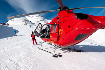 red rescue helicopter stands on the snow-covered mountains of the Austrian Alps