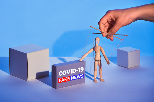 """Covid19 novel coronavirus rumors. Sinister hand control wooden puppet on abstract geometric background. Box with text """"COVID-19 fake news"""". Beware of fake news about outbreak 2019-nCoV treatments!"""