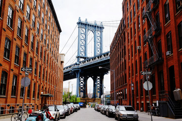Foto op Canvas New York Manhattan bridge seen from a red brick buildings in Brooklyn street in perspective, New York, USA. Beautiful classic apartments in New York City. Beautiful american street. Famous view.