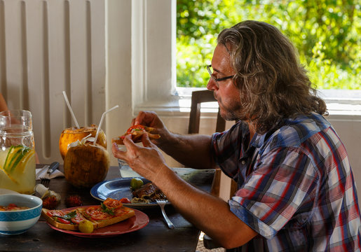man with long black hair and glasses sits at a wooden authentic table and has a healthy Breakfast, coconut, fruit, eggs, vegetables, fruit on the table. Garden terrace, Sunny morning weather.