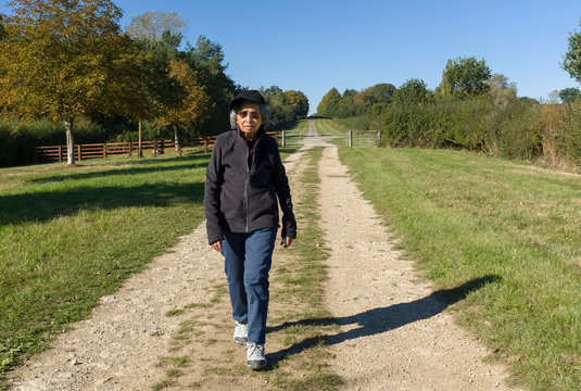 Indian active senior citizen exercising, walking outdoors, UK