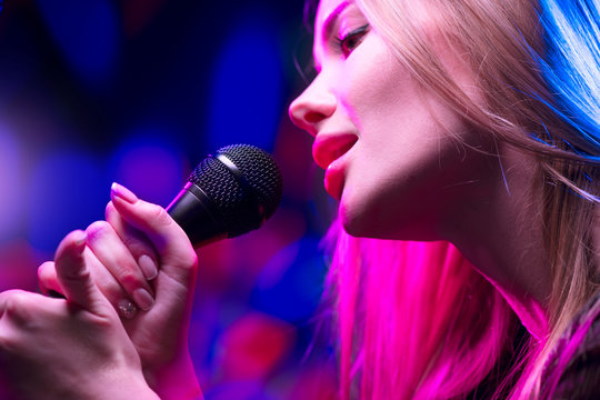Beautiful Singing Girl, Beauty Glamour fashion Woman with Microphone over Blinking bokeh night background. Glamour Model Singer. Karaoke song, party. Rock star singer on music concert.