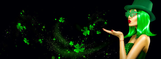 St. Patrick's Day leprechaun model girl pointing hand, holding product, isolated on black magic background, blowing shamrock leaves. Patrick Day pub party, celebrating. Border, Widescreen Wall mural