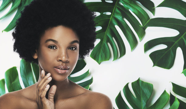 Young and beautiful African woman with perfect smooth skin in tropical leaves