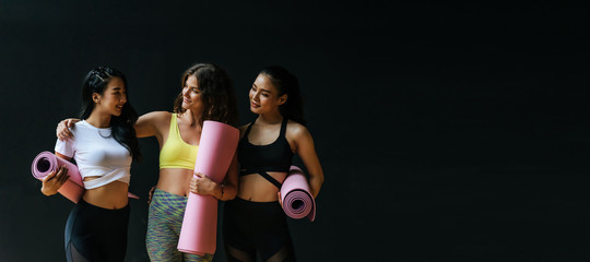 Panoramic banner. group of sporty multicultural women slim body smiling holding yoga mat at dark black wall background in fitness gym resting after yoga class, sport, yoga training, lifestyle concept