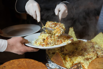 Khan pilaf in a pita. Traditional oriental dish on tableware Azerbaijan with fire on a table in restaurant .the chef cuts off the drill. Shah pilaf.