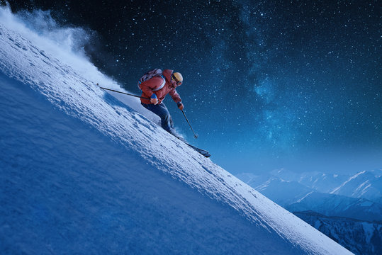skier with a backpack rides freeride on a snowy slope night skiing under a starry sky moonlight
