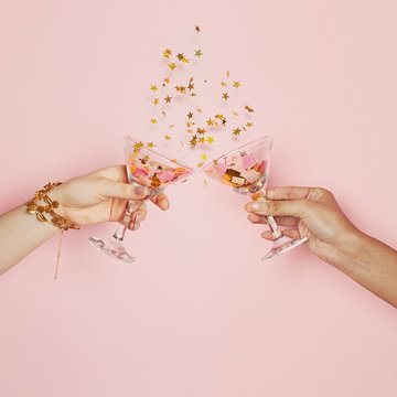 Celebration and holiday background. Two hands holding wine glasses with gold confetti on pink background