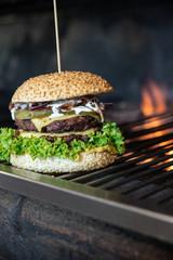 Fototapeta Zdrowy burger grillowany na ogniu. Grillowana kanapka na grillu opalanym drewnem. Slow food, cheesburger ze świeżymi dodatkami.  obraz