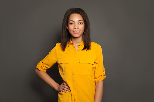 Portrait of happy successful black young woman in yellow shirt on gray studio background