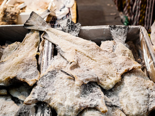 bulk of salted and dried cod fish in a market hall
