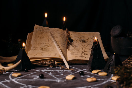 Open old book with magic spells, runes, black candles on witch table. Occult, esoteric, divination and wicca concept.