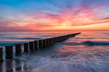 Foto op Canvas Zee zonsondergang Baltic sea seascape at sunset, Poland, wooden breakwater and waves