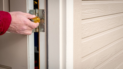 Handy man works on tightening a hinge on a back door