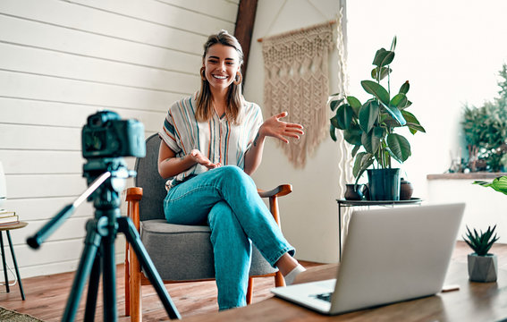 Attractive young woman blogger dressed in jeans and a blouse is recording on the camera while sitting on a comfortable chair at home.