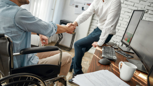 Good deal. Cropped view of male office worker in a wheelchair shaking hand to his colleague while working together in the creative office