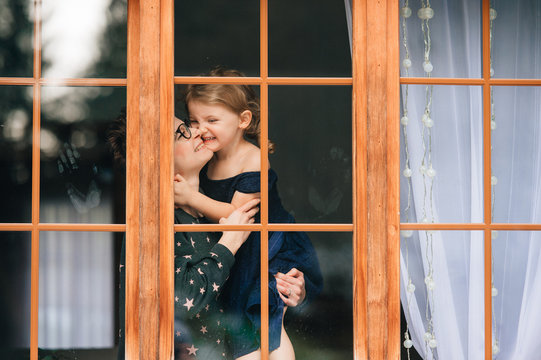 Handsome woman with pretty face hugs a beautiful daughter and looks through big window