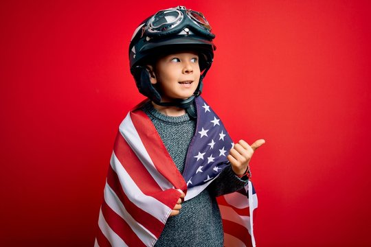 Young little patriotic kid wearing united states of america flag and motorcycle helmet on 4th of July pointing and showing with thumb up to the side with happy face smiling