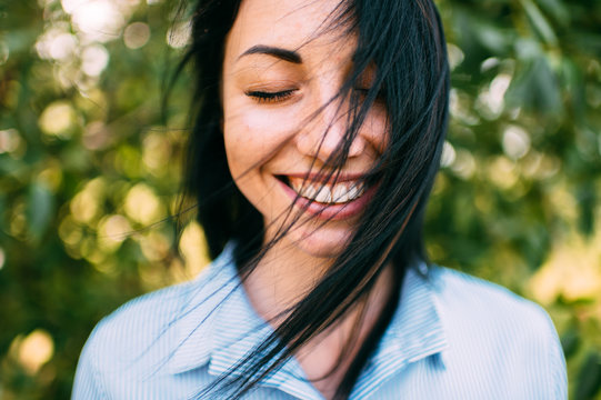 Portrait of beautiful girl with big eyes, long dark hair and pretty smile on the green background