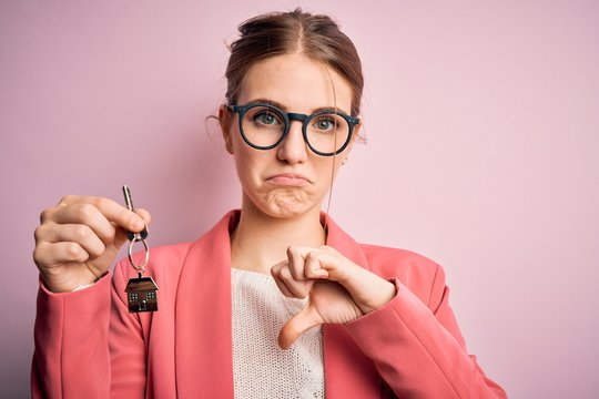 Young beautiful redhead house agent woman holding home key over pink bakcground with angry face, negative sign showing dislike with thumbs down, rejection concept