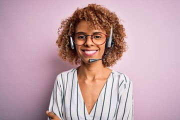 African american curly call center agent woman working using headset over pink background happy face smiling with crossed arms looking at the camera. Positive person.