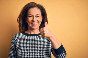Wall Mural - Middle age beautiful woman wearing casual sweater over isolated yellow background doing happy thumbs up gesture with hand. Approving expression looking at the camera showing success.