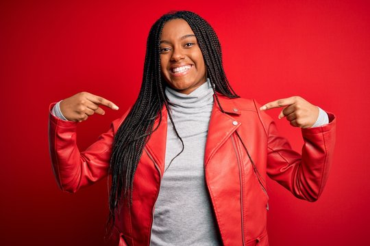 Young african american woman wearing cool fashion leather jacket over red isolated background looking confident with smile on face, pointing oneself with fingers proud and happy.