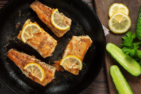Portioned pieces of fried fish in a black cast-iron pan with fresh cucumbers and herbs. Traditional dinner of a village fisherman, top view, flat lay