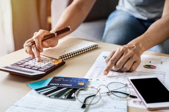 Young woman checking bills, taxes, bank account balance and calculating credit card expenses at home
