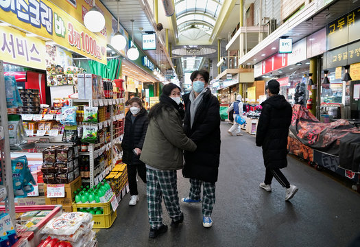 A couple wearing masks to prevent contracting the coronavirus, looks on at an employee from a disinfection service company sanitizing the floor of a traditional market in Seoul