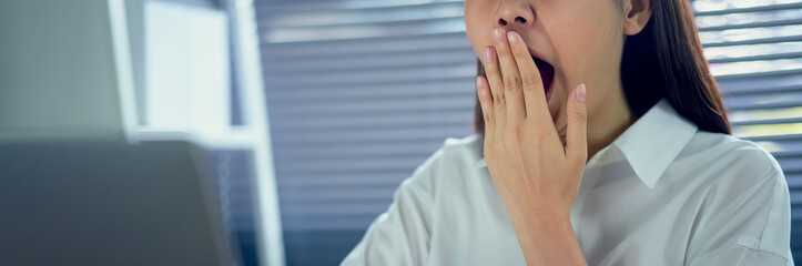 Asian woman yawning covering open mouth and showing a sleepy gesture. feeling being tired from hard work night time.