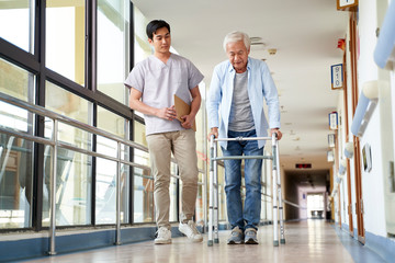 asian old man walking with a walker in rehab center