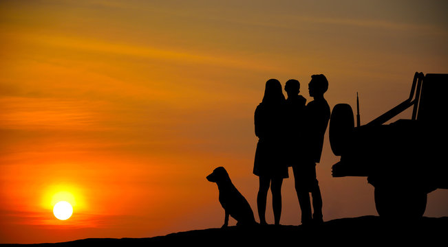 The tourist family and his dog are standing by the car, watching the sunset. Silhouette