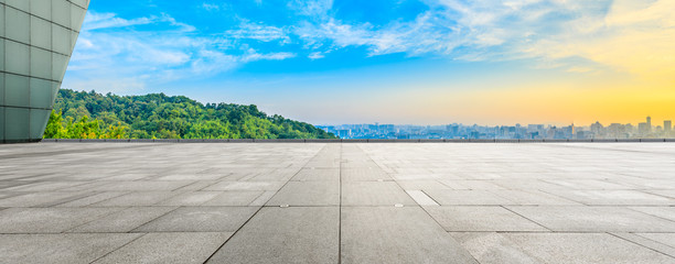 Wide square floor and city skyline with green mountain at sunrise in Hangzhou,China. Wall mural