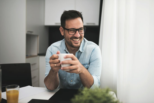 Handsome man having cup of coffee at home in the morning