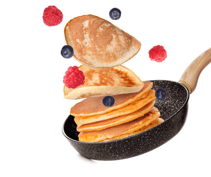 Frying pan with flying pancakes on white background