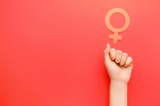 Female hand with symbol of woman on color background. Concept of feminism