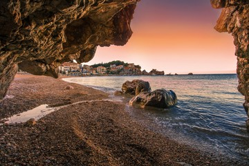 picturesque summer landscape, pebble Pzrno beach near Budva and Sveti Stefan beach, amazing sunset view from little cave, scenic nature wallpaper, Montenegro, Europe