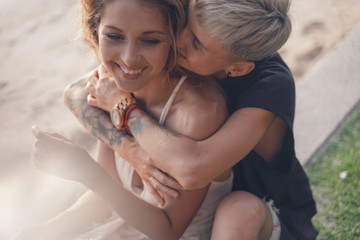 Two beautiful young women in love cuddling tenderly on the beach during a wedding and a honeymoon in the tropics. Love tenderness attraction concept