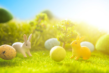 Decorated easter eggs with easter rabbit on grass over sky background