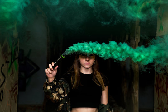 Brown hair girl holds a smoke bomb that throws green smoke around. Young girl wears an urban style, military jacket and piercing. Dark style photography.