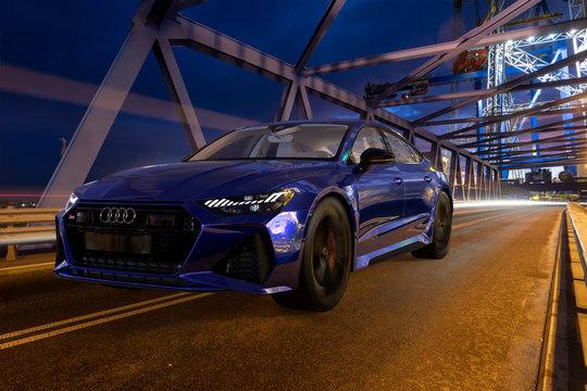 Audi RS 7 driving by illuminated bridge at night