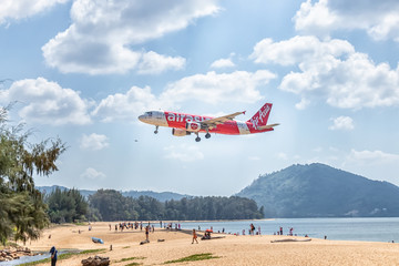 PHUKET, THAILAND - FEBRUARY 1, 2020: AirAsia aircraft ready for landing with many tourists visiting the plane landing spot and enjoy taking pictures of the plane at Mai Khao Beach, near Phuket Airport