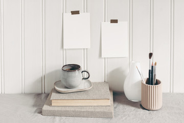 Blank paper cards taped on white wooden wall. Stationery mockup scene with paint brushes, pencils in ceramic holder, cup of coffee and books on linen tablecloth. Artistic scene. Creative background