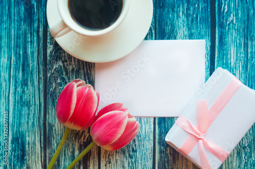 Flat lay photo with coffee cup, gift box and red tulips on wooden background. Beautiful Mother's Day, Women's Day or Valentine greeting card. Mother's Day mockup greeting card