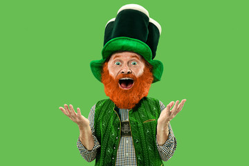 Astonished, surprised. Excited leprechaun in green suit with red beard on green background. Funny portrait of man ready to party. Saint Patrick day, human emotions, celebration, traditional holidays.